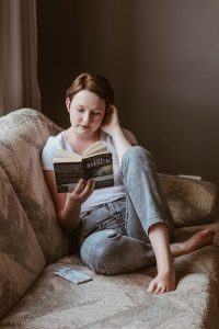 A woman sitting on the couch reading a book