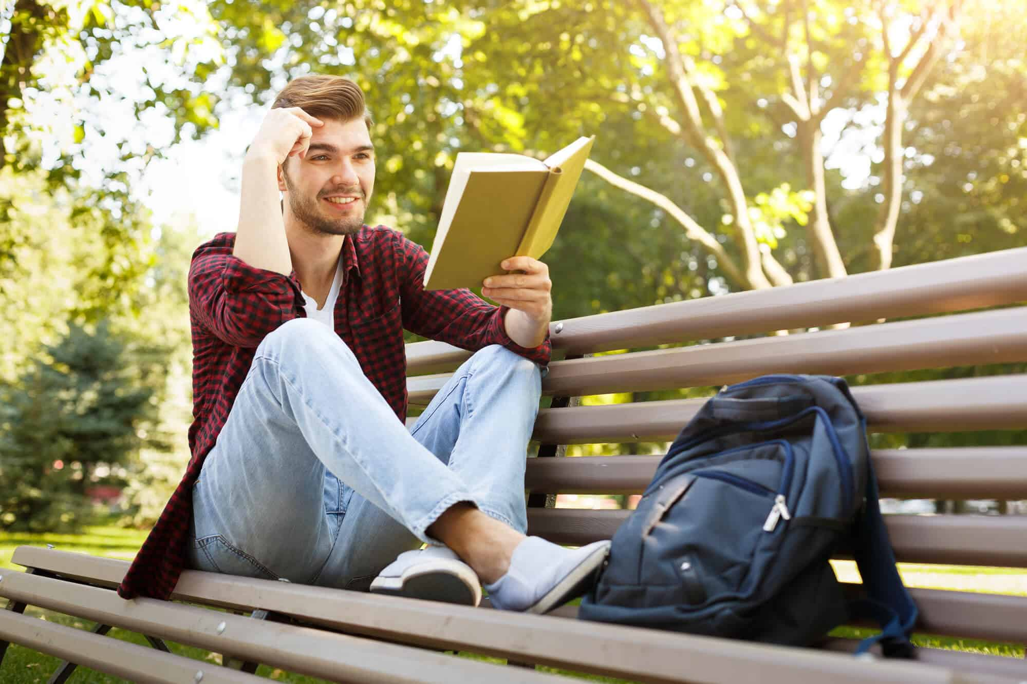 Male college student reading on a bench