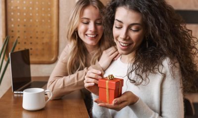 two girls looking at a red gift