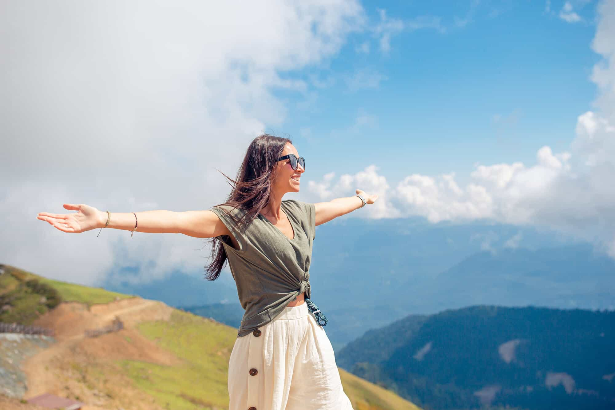 woman looking out over the mountains with her arms outstretched