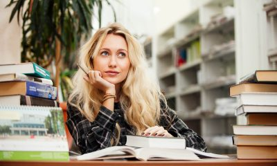a blond girl sitting at a desk with books smiling