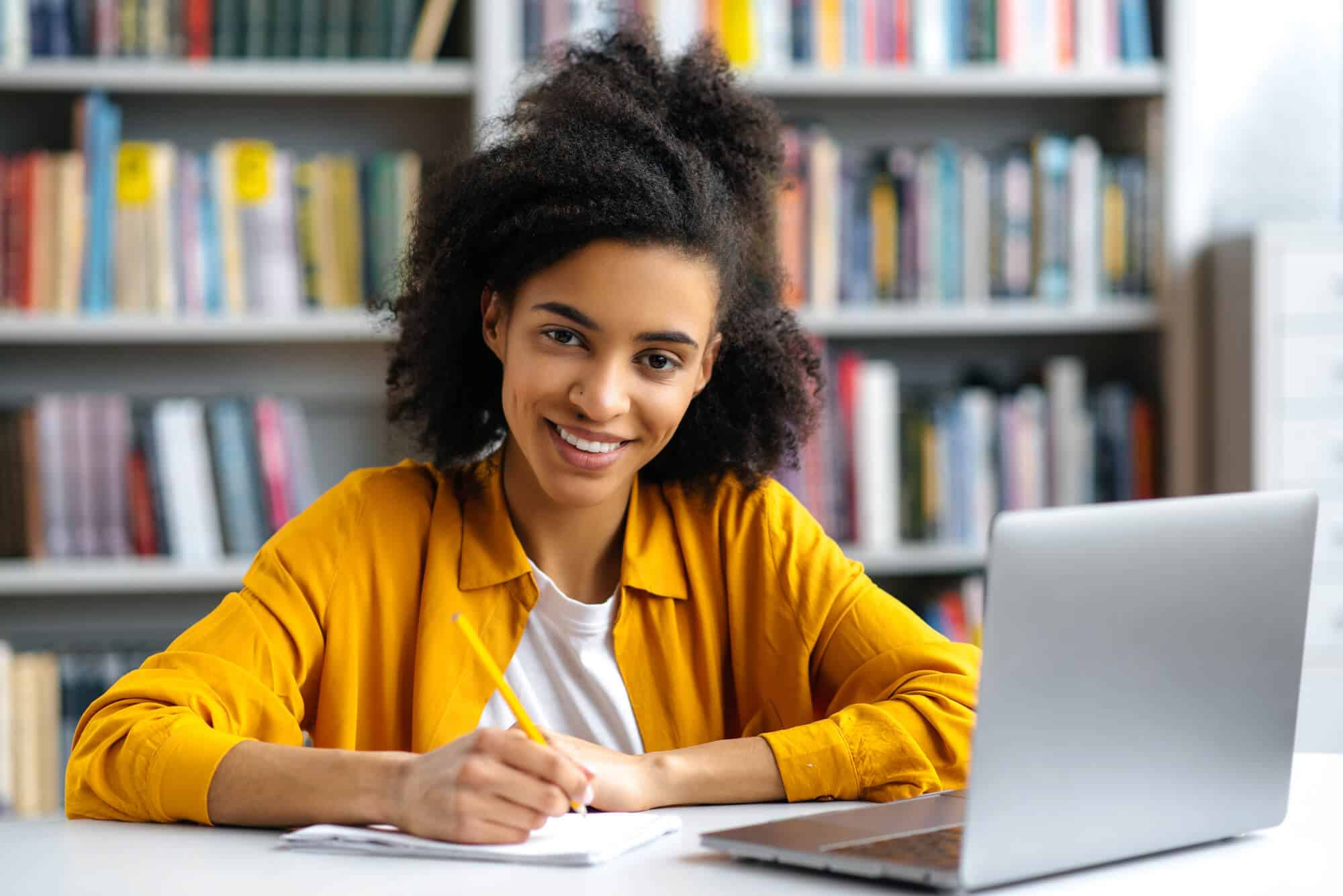 A girl of color sititng at a desk writing and smiling