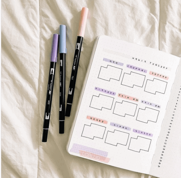 a notebook besides color pencils