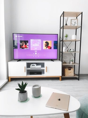 a turned on tv in a white themed living room