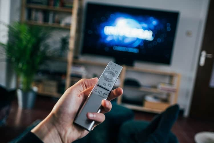 a person holding a remote in front of a TV