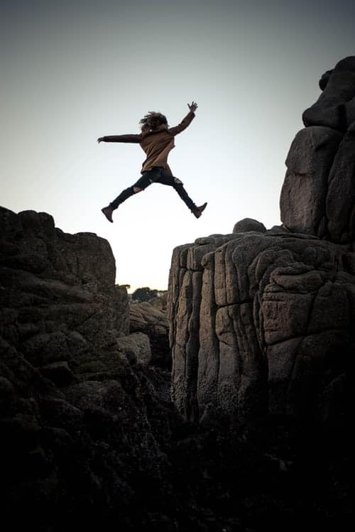 a person jumping between rocks