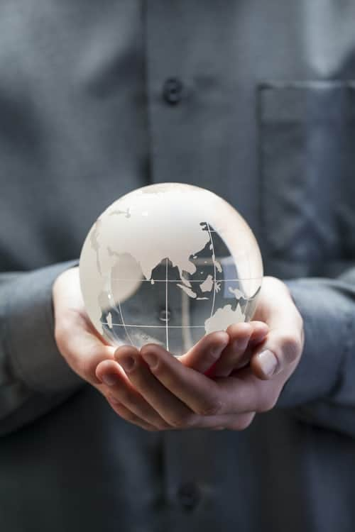 A person holding a clear globe model