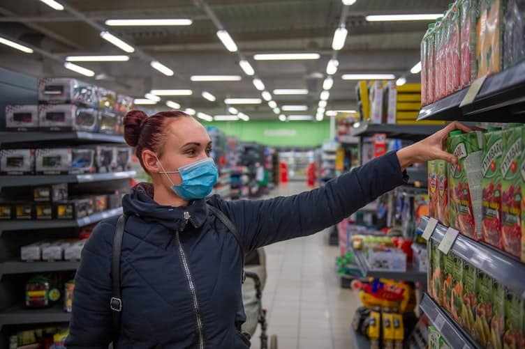 a woman wearing a blue surgical mask shopping in a store