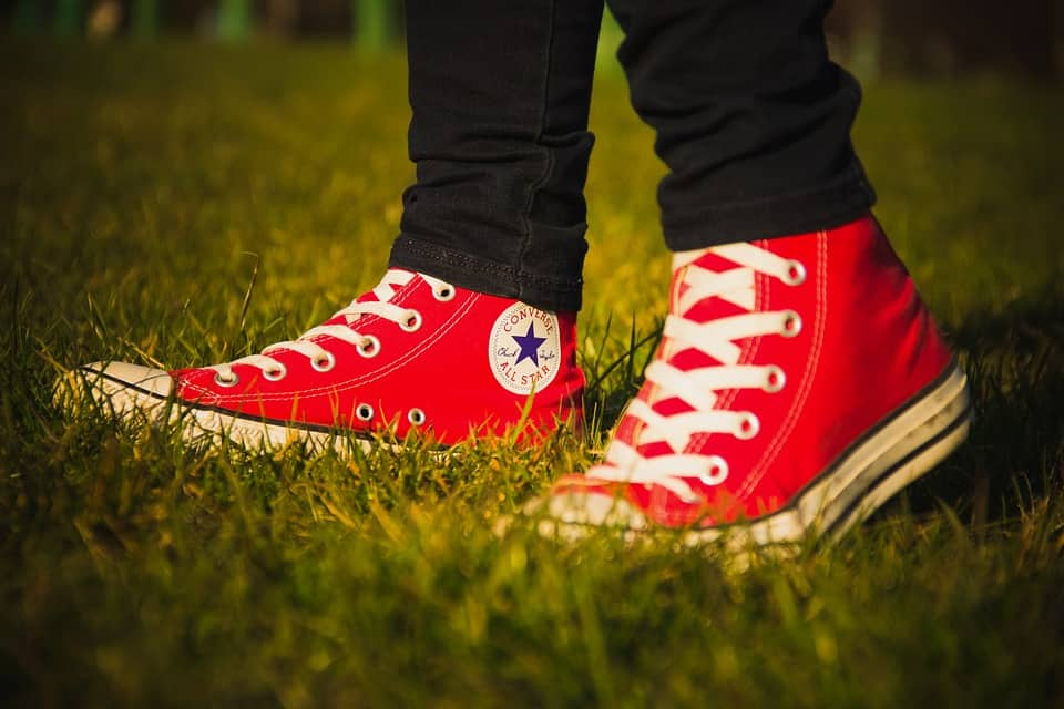 A person wearing red convserse shoes