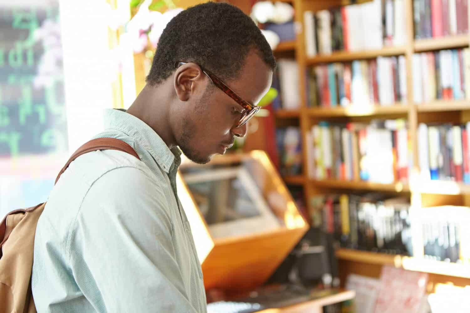student looking at a book in a library