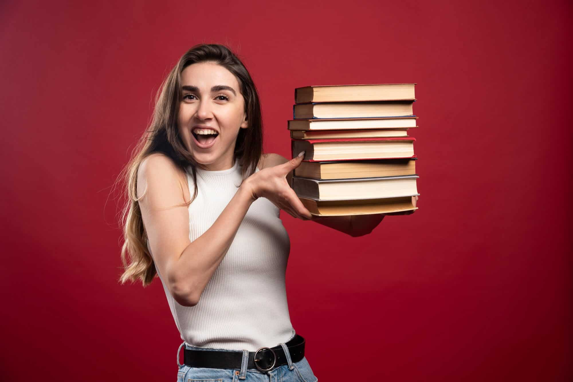 girl carrying a stack of books with red background
