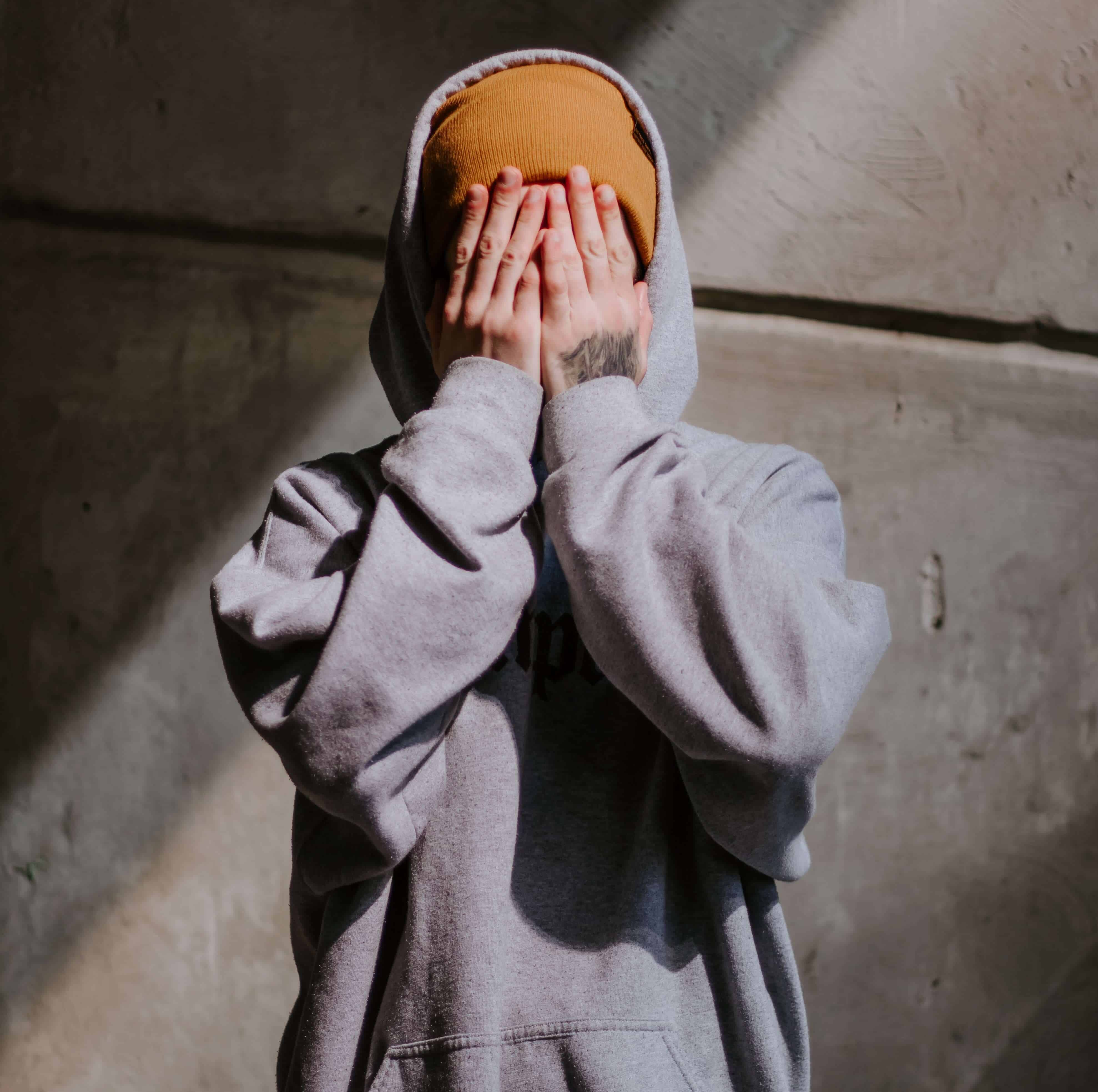 A boy with his hands covering his face wearing a hoodie