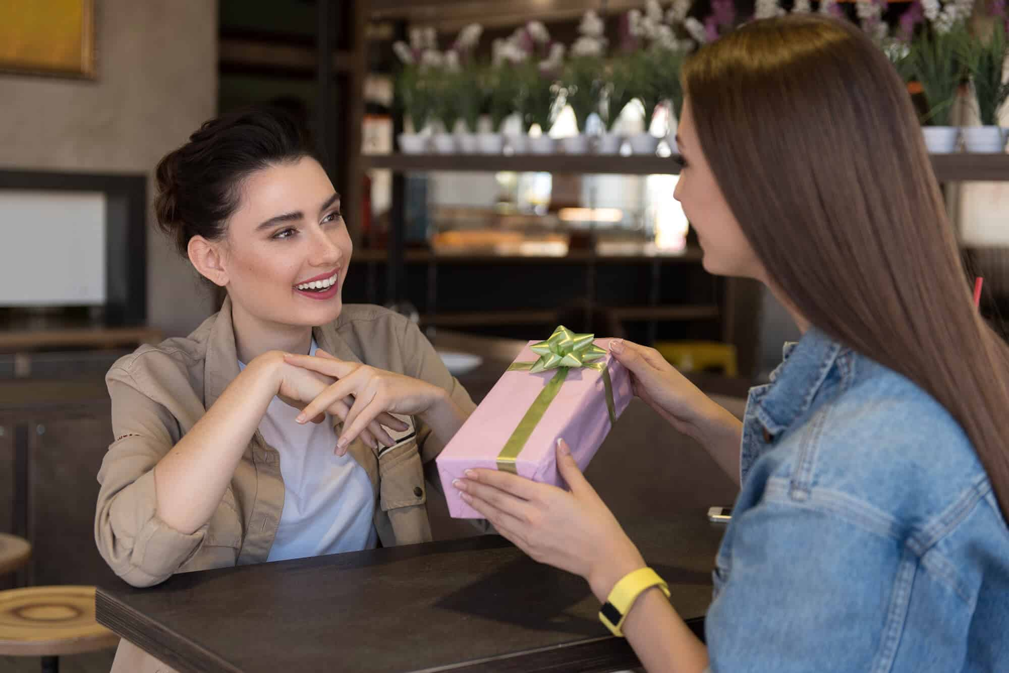 Best friends giving sentimental gifts to each other at a table