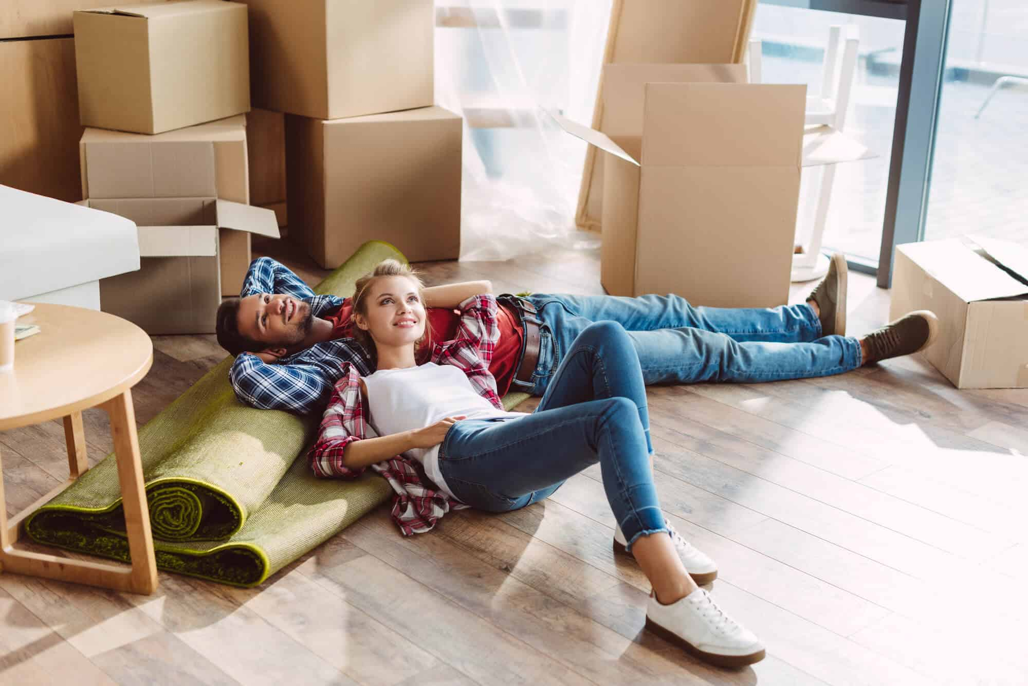 a college couple moving into an apartmnet and laying on the floor with boxes all around them