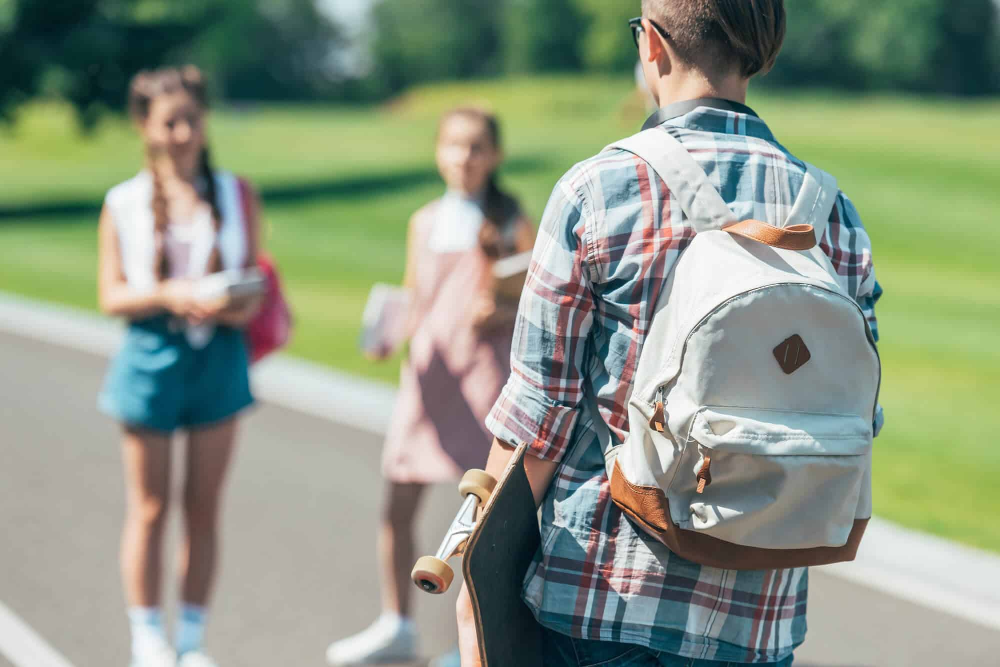 college guy wearing a backpack with other college students in the background