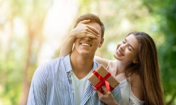 a girl with long hair covering a boy's eyes holding a red gift smiling