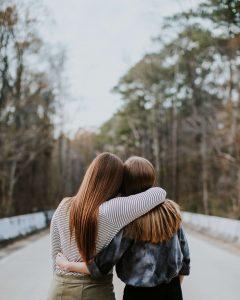Two best friends side hugging on a road