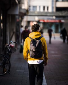 Man with a black backpack and a yellow sweatshirt walking on the street