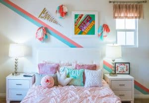 Colorful pillows on a pink bed in a dorm room