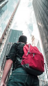 Man with a red backpack in the city